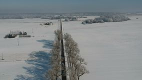 有老树胡同和树冰的,鸟瞰图美丽的冬天乡下公路 股票录像