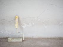 有老混凝土墙的漆滚筒 库存照片