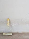有老混凝土墙的漆滚筒 免版税图库摄影