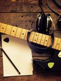 有老演播室耳机的葡萄酒吉他在木头 免版税库存照片