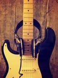有老演播室耳机的葡萄酒吉他在木头 库存图片