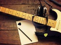 有老演播室耳机的葡萄酒吉他在木头 图库摄影
