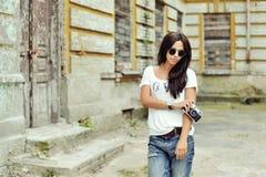 有老照相机佩带的太阳镜的时兴的时髦的女孩和 库存照片