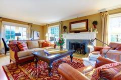有老牌家具和壁炉的迷人的家庭娱乐室 图库摄影