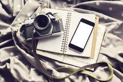 有老牌照相机、日志和书的, m空白的手机屏幕 免版税库存照片
