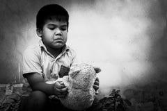 有老玩具熊的孩子叫花子 免版税图库摄影