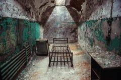 有老生锈的台阶、门和削皮墙壁的被放弃的监狱牢房走道 免版税库存图片