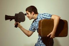 有老电影摄影机的年轻快乐制片商和在他的一个手提箱 库存照片