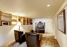 有老电视和两把皮革扶手椅子的古色古香的家庭娱乐室 免版税库存图片