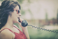 有老电话的女孩 免版税库存图片