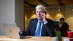 有老白种人的商人特写镜头射击在电话的一次交谈,当使用膝上型计算机户内在时 股票录像