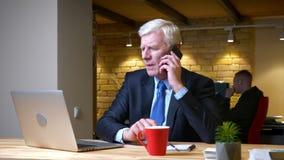 有老白种人的商人特写镜头射击电话,当使用膝上型计算机户内在的时办公室 股票视频