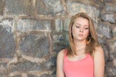 有老石墙的逗人喜爱的女孩在背景中 库存图片