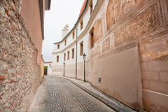 有老石房子和时髦的室外灯的狭窄的街道 库存照片