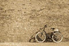 有老砖墙的黑减速火箭的葡萄酒自行车 库存照片