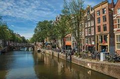 有老砖瓦房、桥梁、小船和蓝天的沿途有树的运河在阿姆斯特丹 库存图片