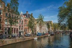 有老砖瓦房的,汽车沿途有树的运河,在阿姆斯特丹停泊了小船和晴朗的蓝天 库存图片