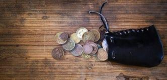 有老硬币的钱包在长的背景中 免版税库存图片