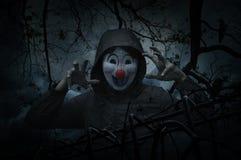 有老篱芭的可怕邪恶的小丑穿戴夹克在死的树,乌鸦 库存图片