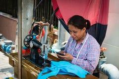 有老缝纫机的街道裁缝在长木凳 免版税库存图片