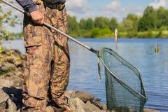 有老网的一位无法认出的中年渔夫与一个孔和一条小新近地被抓的鱼在线 概念 库存图片