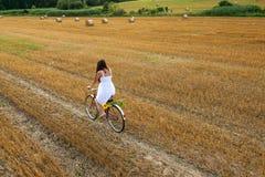 有老自行车的美丽的妇女在麦田 库存图片