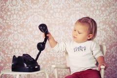 有老葡萄酒电话的小婴孩 免版税图库摄影