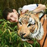 有老虎雕象的男孩 库存照片