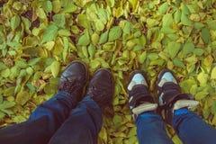 有老运动鞋站立的腿 免版税库存照片