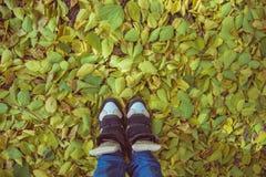 有老运动鞋站立的腿 免版税库存图片
