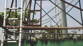 有老金属梯子的葡萄酒生锈的衣裳机架在肮脏的绿色墙壁 免版税图库摄影