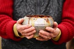 有老铁罐的老妇人用粥在她的手上 传统俄国食物 免版税库存照片