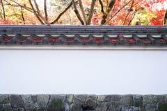 有老铺磁砖的屋顶的日本墙壁有槭树的,红槭叶子墙纸 免版税库存照片