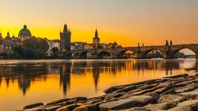 有老镇桥梁塔的查理大桥在伏尔塔瓦河河在早晨日出时间,布拉格,捷克反射了 图库摄影