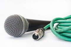 有老绿色xlr缆绳的使用的声音话筒在白色后面 免版税库存图片
