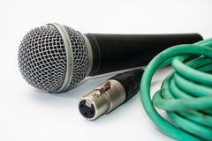 有老绿色xlr缆绳的使用的声音话筒在白色后面 免版税图库摄影