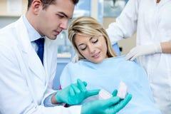 有耐心和牙齿模子的牙医 库存图片