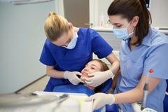有耐心女孩的愉快的女性牙医诊所的 库存照片