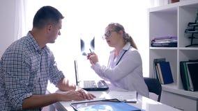 有耐心考虑的X-射线的医生在任命的诊所在医疗办公室 股票录像