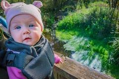 有耳朵帽子的逗人喜爱的婴孩在沼泽地的小型航空母舰自然远足的 免版税库存图片