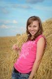 有耳朵的美丽的女孩在手中在干草堆附近 库存图片