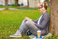 有耳机、片剂个人计算机、书和咖啡的男孩 免版税库存照片