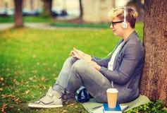 有耳机、片剂个人计算机、书和咖啡的男孩 图库摄影