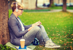 有耳机、片剂个人计算机、书和咖啡的男孩 库存图片