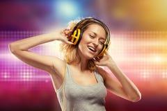 有耳机听的音乐的美丽的妇女 免版税库存图片
