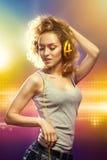 有耳机听的音乐的美丽的妇女 免版税库存照片