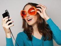 有耳机听的音乐的年轻愉快的妇女 库存照片