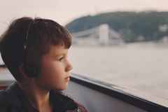 有耳机听的音频的小男孩引导了在多瑙河的游览 免版税库存图片