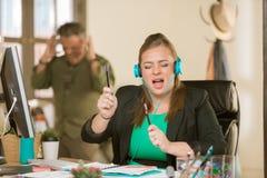 有耳机和使困恼的同事的唱响的妇女 免版税图库摄影