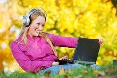 有耳机和户外膝上型计算机秋天的妇女 免版税图库摄影